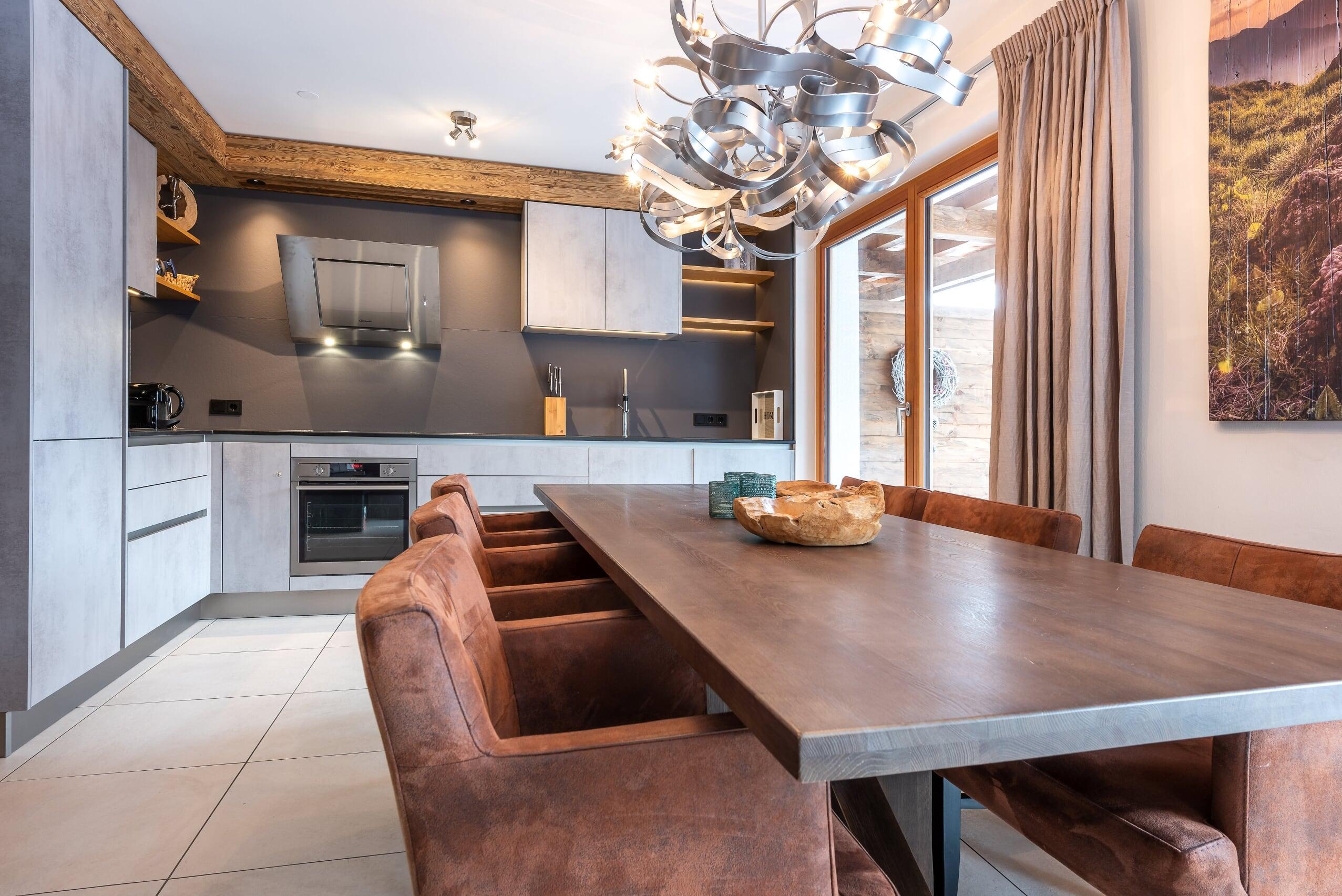 Esstisch mit Küche im Hintergrund - Apartment 3 der Mountain Lodge Leogang